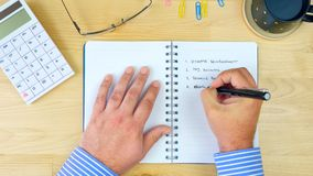 Businessman writing to-do list in notebook, overhead. Businessman accountant writing to-do list in notebook, overhead Stock Photos