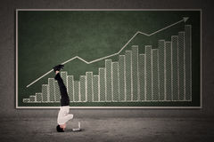 Businessman acrobatic move on profit bar chart Stock Images