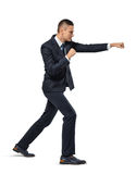 Businessman acting like he is punching someone on a white background. Facing challenges. Tough competition. Fighting spirit royalty free stock photography