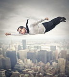 Businessman acting like a superhero. And flying over the city royalty free stock photography
