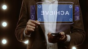 Businessman shows hologram with text Achieve. Businessman activates conceptual HUD hologram on smartphone with text Achieve. Man in a white shirt and jacket with stock footage