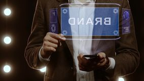 Businessman shows hologram with text Brand. Businessman activates conceptual HUD hologram on smartphone with text Brand. Man in a white shirt and jacket with a stock video