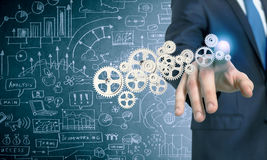 Businessman activating gears mechanism royalty free stock photo