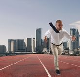 Businessman acts like a runner. Competition and challenge in business concept. Businessman acts like a runner on a track. Competition and challenge in business Stock Photography