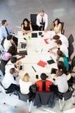 Businessman Addressing Meeting Around Boardroom Table. Having A Conversation stock photos