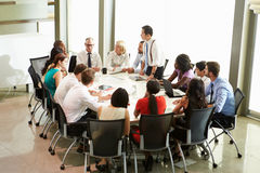 Businessman Addressing Meeting Around Boardroom Table Royalty Free Stock Photos