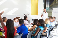 Businessman Addressing Meeting Around Boardroom Table. Looking At Colleagues Smiling royalty free stock images