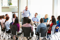 Businessman Addressing Multi-Cultural Office Staff Meeting. Standing Up Talking Royalty Free Stock Photography