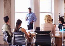 Businessman Addressing Team Meeting Around Table Royalty Free Stock Images