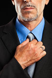 Businessman adjusting collar. Sophisticated businessman adjusting his tie Royalty Free Stock Photography