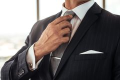 Businessman adjusting his necktie Stock Photos