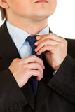 Businessman adjusting his tie. Close-up. Royalty Free Stock Images