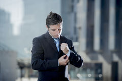 Businessman adjusting shirt cuff link outdoors exterior office building Royalty Free Stock Image