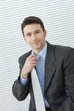 Businessman adjusting tie. Portrait of happy young businessman at office wearing grey suit and blue shirt, adjusting his tie, smiling Stock Image