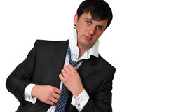 BUSINESSMAN ADJUSTING TIE. Portrait of a young businessman on isolate white background wearing black suit and white shirt, putting his tie on Stock Photography
