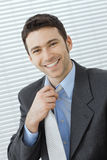 Businessman adjusting tie Stock Image