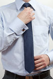 Businessman adjusting tie. Body of young businessman in shirt adjusting or fastening tie royalty free stock images