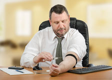 Businessman administers medication into his vein Royalty Free Stock Image