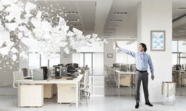 Businessman with aerosol can. Businessman in office interior spraying paint from aerosol Royalty Free Stock Photos