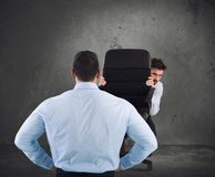 Businessman is afraid of his boss. Employee hiding behind chair is afraid of his boss stock images