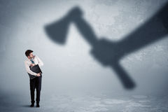 Businessman afraid of a huge shadow hand holding an axe concept Royalty Free Stock Photos