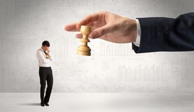Businessman is afraid to make the next step in a chess game with graphs background royalty free stock photography
