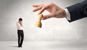 Businessman is afraid to make the next step in a chess game with graphs background royalty free stock photos
