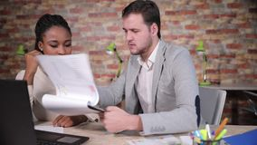 Businessman with afro american woman discuss business plan. Beautifull afro american secretary shows to the businessman documents, details of information in stock footage