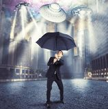 Businessman against alien attack. Businessman protects himself from an alien attack stock image
