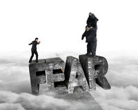 Businessman against bear balancing on fear 3D word with cloudy Royalty Free Stock Images