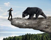 Businessman against black bear balancing on cliff with sky trees Royalty Free Stock Photo