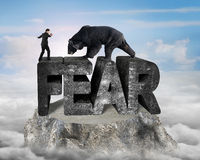 Businessman against black bear standing on fear 3D concrete word Stock Images