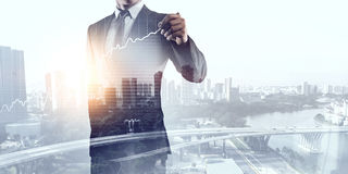 Businessman against modern city background . Mixed media Stock Images