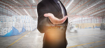 Businessman against modern warehousing Royalty Free Stock Images