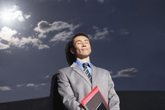 Businessman Against Reflective Wall With Eyes Closed Royalty Free Stock Photo