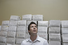 Businessman Against Stack Of Filing Boxes Stock Photography