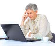 The businessman at the age of works for the laptop. Stock Photo