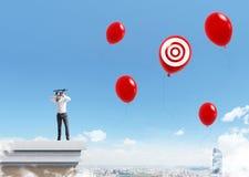 Businessman aiming at balloons Stock Image