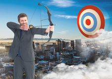 Businessman aiming with bow and arrow at target over cityscape. Digital composition of businessman aiming with bow and arrow at target in sky over cityscape Stock Image