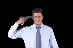Businessman aiming a handgun at his head Royalty Free Stock Photography
