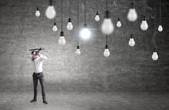 Businessman aiming at lightbulbs Royalty Free Stock Image