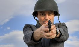 Businessman aiming pistol. A view of a businessman wearing a steel helmet and stiffly pointing a pistol directly ahead.  Isolated against a blue sky and clouds Royalty Free Stock Image