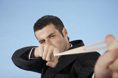 Businessman Aiming Rubber Band On Blue Background Royalty Free Stock Images