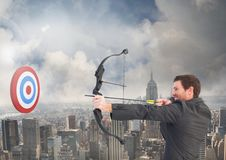 Businessman aiming at the target board against cityscape in background Stock Photography