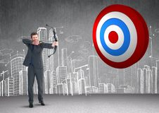 Businessman aiming at the target board against hand drawn cityscape in background. Digital composition of businessman aiming at the target board against hand Stock Image