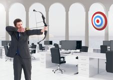Businessman aiming at the target board against office in background Stock Image