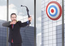 Businessman aiming at the target board against office buildings in background Royalty Free Stock Photography