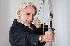 Businessman aiming at target with bow and arrow. Portrait of successful businessman aiming at target with bow and arrow Royalty Free Stock Image