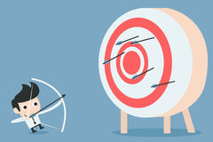 Businessman aiming at target with bow and arrow stock photography