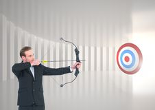 Businessman aiming at target with bow and arrow Stock Photo